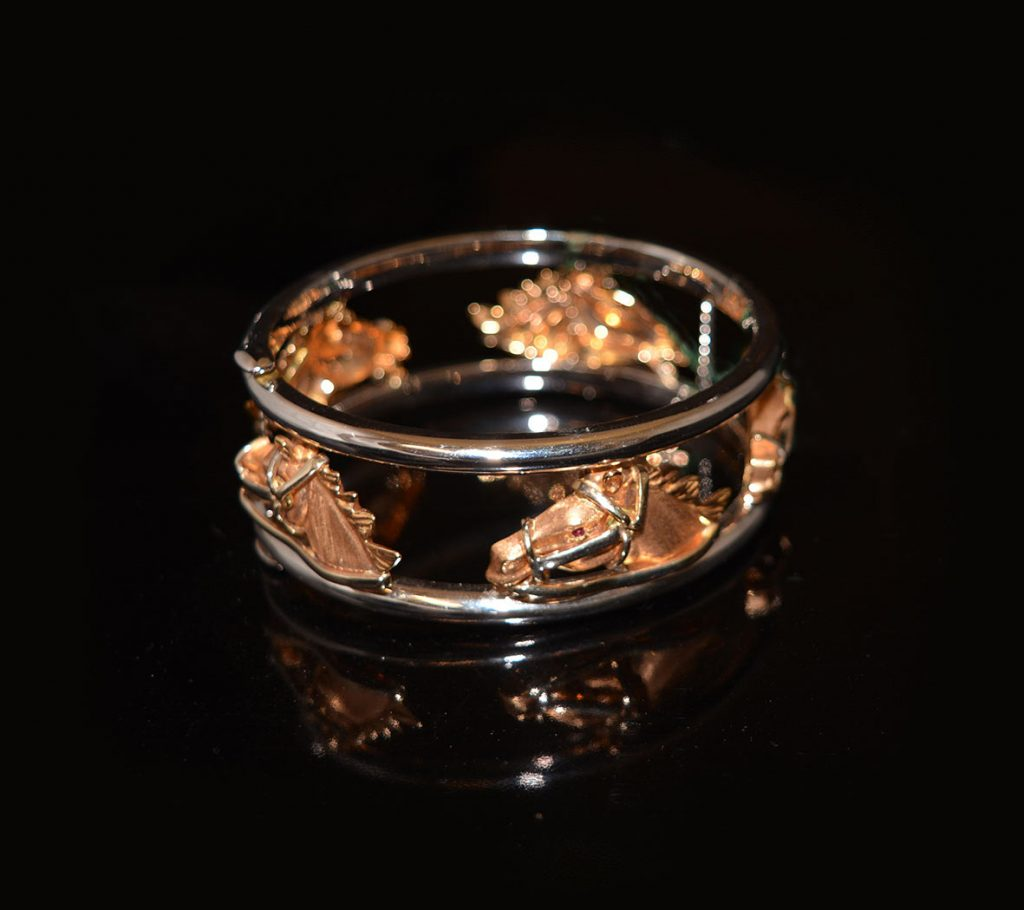 Merry Go Round bangle. Yellow and white gold studded with rubies. £3750.00